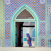 A pilgrim walks in front of an ornately tiled entry to the Shrine to Hazrat Ali, in Mazar-i-Sharif, Afghanistan.