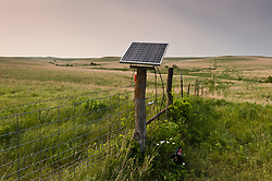 A solar panel powers an electric fence used for controlling cattle and bison along the Windmill and West Traps pastures at the Tallgrass Prairie National Preserve. The electric fence is powered by a Kyocera Photovoltaic Module (Model KC5COT) solar panel that is connected to a fence battery system manufactured by Taylor Fence, Inc. (Cyclops Power on Demand Brute Battery). The 10,894-acre Tallgrass Prairie National Preserve is located in Chase County near the towns of Strong City and Cottonwood Falls. Less than four percent of the original 140 million acres of tallgrass prairie remains in North America. Most of the remaining tallgrass prairie is in the Flint Hills in Kansas. Tallgrass Prairie National Preserve is the only unit of the National Park Service dedicated to the preservation of the tallgrass prairie ecosystem. The Tallgrass Prairie National Preserve is co-managed with The Nature Conservancy.