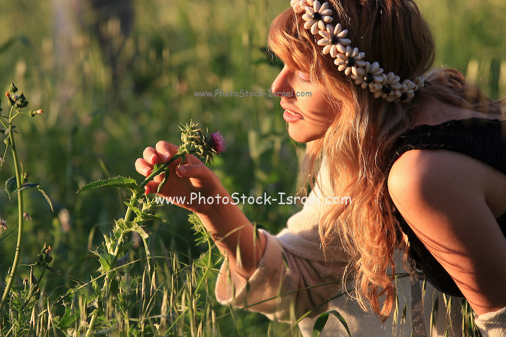 Young woman of 25 smells a wildflower