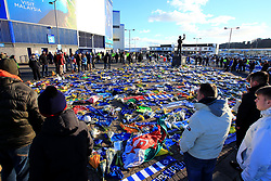 Fans looking on at the flowers and scarves placed outside Cardiff City Stadium in tribute to Emiliano Sala during the Premier League match at the Cardiff City Stadium.