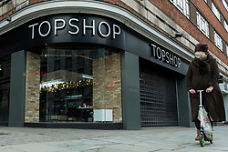 © Licensed to London News Pictures. 28/01/2021. LONDON, UK. A woman passes a branch of Topshop on Oxford Street, the traditional home of retail in the West End. Online retailer Asos is reported to be interested in buying the parts of the business from owner Arcadia which recently collapsed into administration.  Already suffering from competition from online shopping, the coronavirus pandemic has resulted in reduced footfall and lockdowns have forced non-essential shops to close.  Photo credit: Stephen Chung/LNP