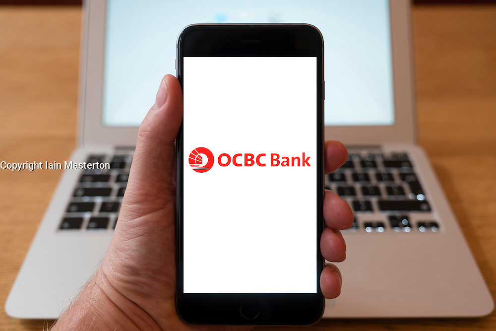 Using iPhone smart phone to display website logo of OCBC Bank, Oversea-Chinese Banking Corporation, based in Singapore
