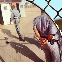 Guards stand waiting in the prison yard.    (Photo by Kim Christensen)
