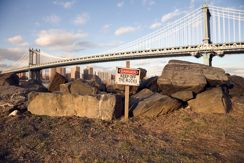 large Danger keep off the rocks sign by some small rocks with Manhattan Bridge in the background