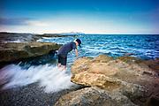 son serra de Marina, Mallorca, Boy is looking for shells between the rocks . 16-08-2018