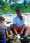 Boys gutting fish, Cayman Brac, Cayman Islands,