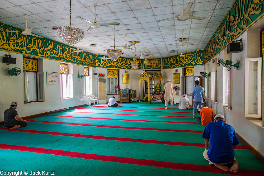 21 FEBRUARY 2013 - BANGKOK, THAILAND:   Men gather for noon prayers in the Haroon Mosque in Bangkok.  Haroon Mosque, originally known as Masjid Ton Samrong, is one of the first mosques in Bangkok and was originally built in the middle of the 19th century. It was established by Musa Bafadel, an Indonesian trader from Pantiyanah, south of Borneo in what is now Indonesia. The mosque is now named after Haroon, Musa Bafadel's son who inherited his father's trade empire. The mosque was originally built of wood, but the wood decayed in Bangkok's climate and is now built of bricks and mortar. The wood was salvaged and used in the construction of the mosque.      PHOTO BY JACK KURTZ