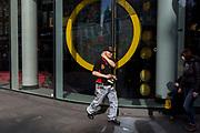 A chinese man walks from Chinatown in Soho, past the M@M store in Leicester Square, on 21st March 2017, in London, England.