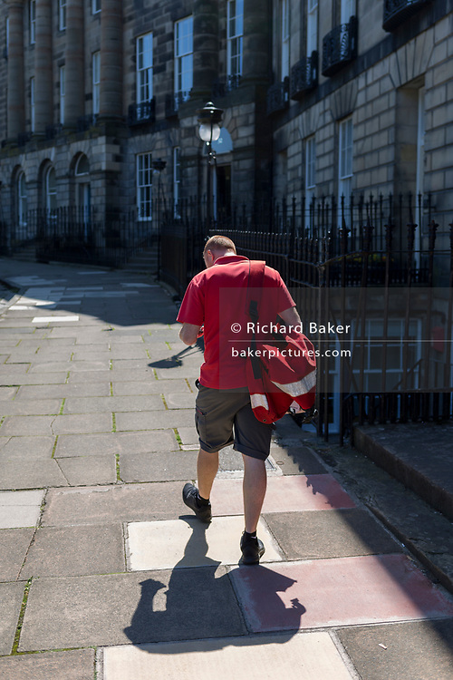 A postman delivers mail on Moray Place in Edinburgh, on 26th June 2019, in Edinburgh, Scotland.