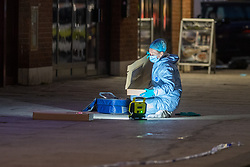 © Licensed to London News Pictures. 23/04/2021. London, UK. A forensic investigator recovers a metal pole on Barking Road in Canning Town following the fatal stabbing of a 14-year-old boy. Police were called at 15:56 BST on Friday, 23 April to reports of an assault in Barking Road, E16. Metropolitan Police officers attended with medics from the London Ambulance Service and the London Air Ambulance. They found a 14-year-old male who had been stabbed. He was pronounced dead shortly after 16:30 BST. Photo credit: Peter Manning/LNP