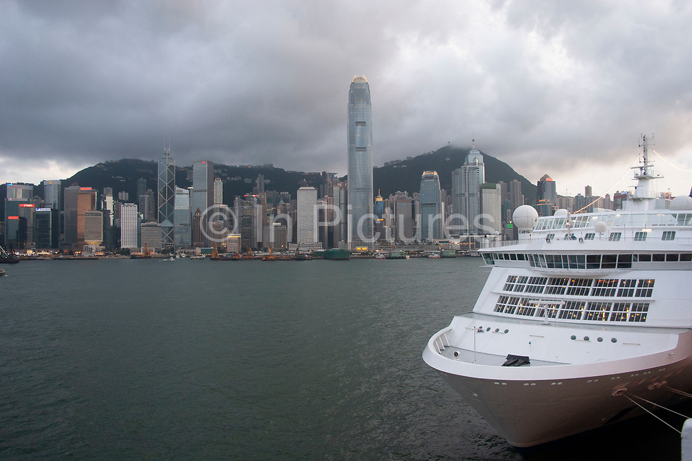Cruise Liner moored on the Kowloon side of Hong Kong Harbour, Hong Kong, China. Many cruise ships pass through the waterway or moor for the night to offer passengers a chance to watch the dramatic skyline develop and light up. Clouds form over the peak at nightfall and collect over Hong Kong's dramatic night skyline. Many of Hong Kong's distinctive buildings line up including the once dominant Bank of China building. Two International Finance Centre now towers over the skyline at 88 stories 415m tall, lighting up the clouds it nearly reaches. A classic blue Hong Kong sky forms a backdrop for the forming clouds.