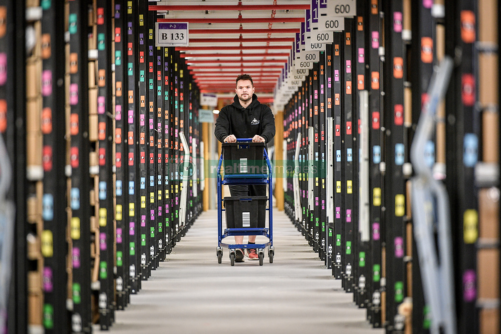 Embargoed to 0001 Friday November 16 A worker walks between thousands of racks at Amazon's fulfillment centre in Swansea, in the run up to Black Friday.