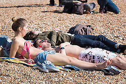 © Licensed to London News Pictures. 25/03/2016. Brighton, UK.  A young couple in swimwear as Thousands of people relax in the sun on Brighton Beach at the start of the Easter Bank Holliday weekend. Photo credit: Hugo Michiels/LNP