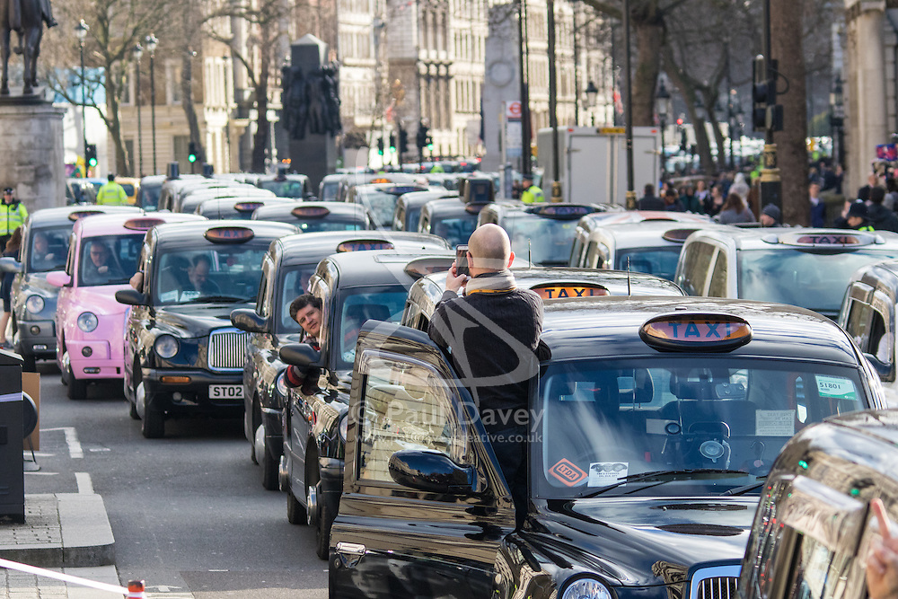 Whitehall, London, February 10th 2016. Taxis begin to fill up Whitehall as an estimated 8,000 cabbies hold a go-slow in protest against what they say is unfair competition from minicab and Uber drivers who do not have to undergo the rigorous training and checks required for the licenced taxi trade. ///FOR LICENCING CONTACT: paul@pauldaveycreative.co.uk TEL:+44 (0) 7966 016 296 or +44 (0) 20 8969 6875. ©2015 Paul R Davey. All rights reserved.