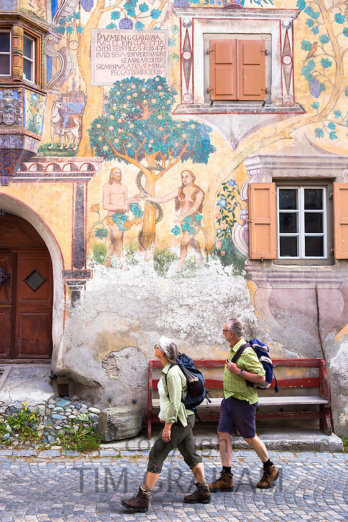 Tourists pass Adam and Eve mural in the Engadine Valley village of Ardez with painted 17th Century houses, Switzerland