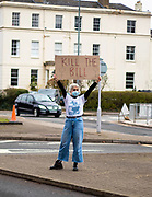 """A woman holding the sign """"Kill The Bill"""" stands in the middle of the road peacefully protesting the newly introduced restrictions of the right to protest. Cheltenham 20/03/2021"""
