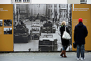Berlin 1990. Impoverished former East Germans sell artifacts from the former DDR sitting on the 'Western' side of Check Point Charlie, seen in the background. Part of the Berlin Wall can be seen on the right background..COPYRIGHT PHOTOGRAPH BY BRIAN HARRIS  © 1990.07808-579804