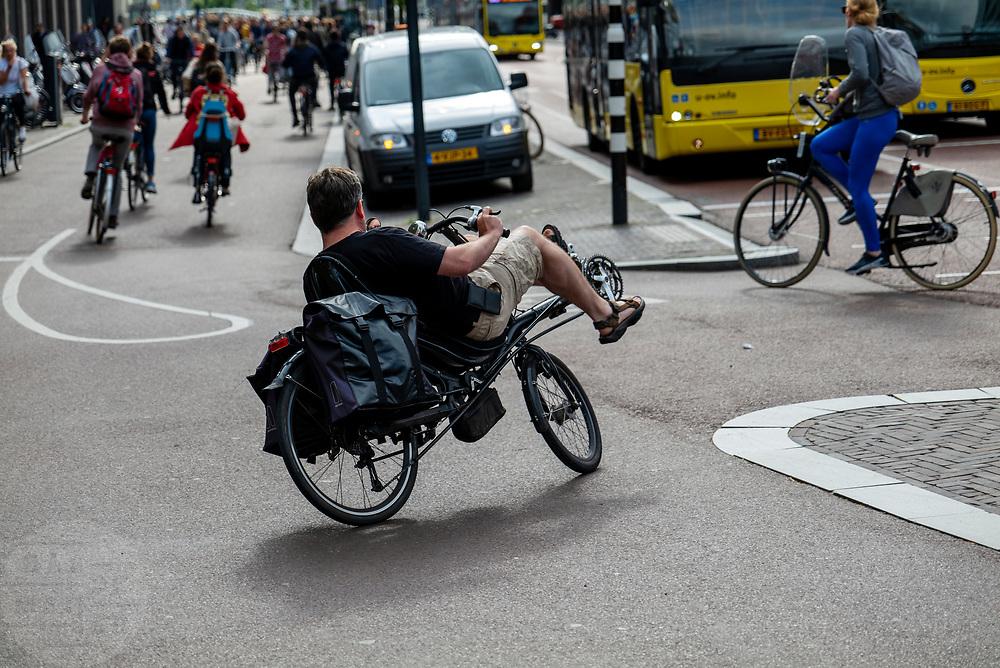 In Utrecht rijdt een ligfietser in de avondspits het fietspad langs het Vredenburg op.<br /> <br /> In Utrecht a recumbent cyclists turns to the bike lane during rush hour,