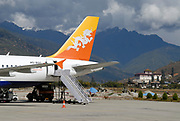 A Druk Air flight on the runway at Paro airport, PBH. The Thunder Dragon, Druk, nation symbol of Bhutan is also the symbol of the airline and can be seen on the tail. Paro Dzong can be seen in the background. Paro, Druk Yul, Kingdom of Bhutan. 10 November 2007