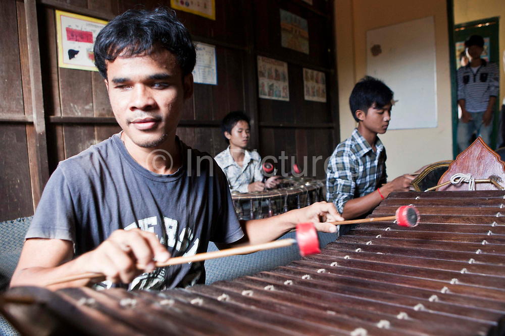 A group of teenagers having a music lesson in the Krousar Thmey school for Deaf and Blind children in Phnom Penh. The Krousar Thmey Foundation assists underprivileged children across Cambodia.