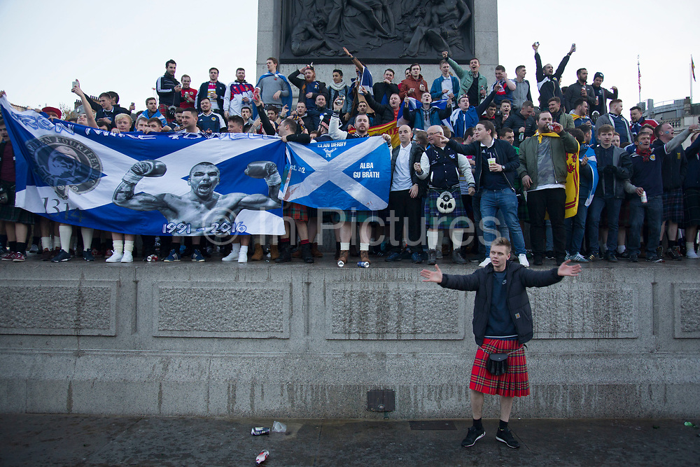 Scotland fans wearing kilts in joyous mood drinking and singing together in Trafalgar Square ahead of their football match, England vs Scotland, World Cup Qualifiers Group stage on 11th November 2016 in London, United Kingdom. The Home International rivalry between their respective national teams is the oldest international fixture in the world, first played in 1872.