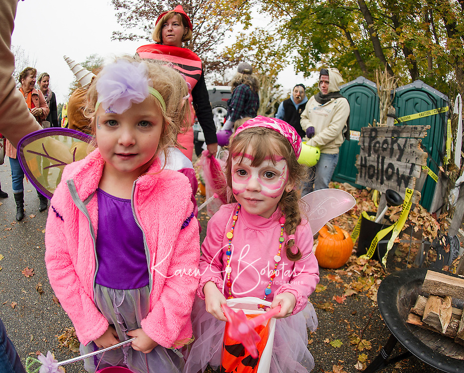 """Kailey Knott and Paige Fusonie go """"trick or trunking"""" through Mandie and Ian Hagan's """"Poopy Hollow"""" display during Holy Trinity's Halloween parade Thursday afternoon.  (Karen Bobotas/for the Laconia Daily Sun)"""
