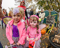 "Kailey Knott and Paige Fusonie go ""trick or trunking"" through Mandie and Ian Hagan's ""Poopy Hollow"" display during Holy Trinity's Halloween parade Thursday afternoon.  (Karen Bobotas/for the Laconia Daily Sun)"