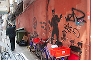 Modern graffitti art on a back street lane behind a restaurant in Wan Chai district, Hong Kong, China. A waiter dressed in black takeing a cigarette break in the lane mirrors the black figure depicted in the graffitti.