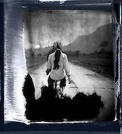 Old polaroid photo. Rear view of a couple riding on their bicycle on a concrete road going through the countryside. Palawan island, Philippines, Asia.