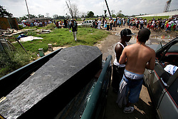 29 August 2006. New Orleans, Louisiana. Lower 9th ward. <br /> One year later and people gather at the site of the breach of the industrial canal for the Great Flood commemoration and memorial ceremony to 'honor and remember our loved ones who have passed.' A mock coffin sits in the back of a pick up truck as people came to mark the anniversary of devastating hurricane Katrina at the site where the now repaired and allegedly in theory stronger levee flood wall. The levee breached along the industrial canal at the point where people gathered, needlessly killing hundreds of innocent civilians in the worst engineering disaster in US history.