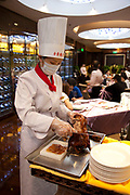 Female chef carves a roast duck in the traditional manner in the main dining room, slicing the breast meat into thin slices, each with a small pieve of the savoured fat. She is the only duck chef in Beijing.  Quanjude roast duck restaurant in Wangfujing, Beijing. This is a Chinese restaurant known for its trademark Peking Roast Duck and is known for being the best roast duck restaurant in China. Quanjude was established in 1864 during the Qing Dynasty under the reign of the Tongzhi Emperor. Although Peking Duck can trace its history many centuries back, Quanjude's heritage of roast duck preparation - using open ovens and non-smoky hardwood fuel such as Chinese date, peach, or pear to add a subtle fruity flavor with a golden crisp to the skin, was originally reserved for the imperial families.