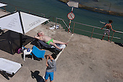 Sunbathers and a stretching youth in Cascais, near Lisbon, Portugal.