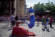 """A street perfomer who refers to  """"Aladdin and the magic lamp"""" perfoming in-front of a crowd at Old Town Square."""