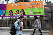 Bolivia 2013. La Paz. Banner celebrating Law against sexual violence, saying in Spanish Ahora si, Libres de violencia ( Now we are free of violence) with photographs of a variety of smiling women , with two women passing.