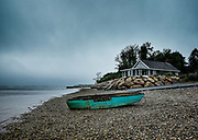 Secluded waterfront bungalow with wooden rowboat.