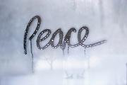 """""""Peace"""" written on foggy winter window"""
