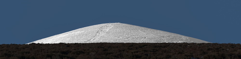 Snow Covered Djouce Mountain.<br /> Sunshine and snow make this mountain a wonderful subject on a freezing cold day in January, 2021. The simple shapes and the three separate blocks of colour caught my eye.