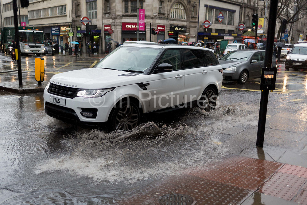 A Range Rover splashes through rain water as Storm Georgina swept across parts of Britain and in central London, lunchtime office workers were caught out by torrential rain and high winds, on 24th January 2018, in London, England. Pedestrians resorted to leaping across deep puddles at the junction of New Oxford Street and Kingsway at Holborn, the result of overflowing drains.