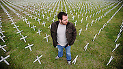 Youth pastor looks over field of crosses.