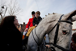 © Licensed to London News Pictures. 26/12/2012. Tenterden, Kent. The Whip of the hunt, Terry Chapple welcomes a child onto his horse during the Ashford Valley Hunt meet and greet in Tenterden on Boxing Day. Photo credit : Rebecca Mckevitt/LNP