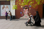 A Muslim mother with her children walks past the mural of iconic musician and singer David Bowie has appeared on the wall of Morleys department store in Brixton, Lambeth, south London. The Bowie face is sourced (by an unknown artist) from the cover of his 1973 album Aladdin Sane at the height of his 1970s fame. The pop icon lived at 40 Stansfield Road, Brixton, from his birth in 1947 until 1953. This cover appeared in Rolling Stone's list of the 500 greatest albums of all time, making #277.
