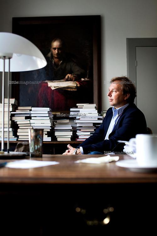 Oslo, Norge, 17.07.2012. Mads Nygaard i Ascheoug forlag fotografert på sitt kontor. På veggen henger et portrett av Andre Bjerke malt av Odd Nerdrum i 1977/78. Foto: Christopher Olssøn.
