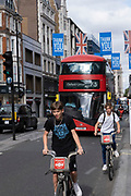 With most shops now open but with retail sales suffering due to the Coronavirus pandemic, young adults not wearing face maks, which will become compulsory in shops on the 24th July, come to Oxford Street on their bike hire cycles, Londons main shopping district on 16th July 2020 in London, United Kingdom. Coronavirus or Covid-19 is a respiratory illness that has not previously been seen in humans. While much or Europe has been placed into lockdown, the UK government has put in place more stringent rules as part of their long term strategy, and in particular social distancing.