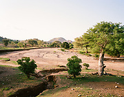 """NUBA MOUNTAINS, SUDAN – JUNE 9, 2018: A view near Kouda, the primary cultural center for the Nuba in Hieban County.<br /> <br /> In 2011, the government of Sudan expelled all humanitarian groups from the country's Nuba Mountains. Since then, the Antonov aircraft has terrorized the Nuba people, dropping more than 4,080 bombs on hospitals, schools, marketplaces and churches. Today, vestiges of the Antonov riddle the landscapes of daily life, where more than 1 million Nuba live in famine conditions – quietly enduring the humanitarian blockade intended to drive them out of the region. The skies are mostly clear. Yet the collective memory of the bombings remains an open wound, and the Antonov itself a persistent threat. So frequent were the attacks that the Nuba nicknamed the high flying aircraft and its dismal hum: """"Gafal-nia ja,"""" they would declare, running to the hillsides. """"The loss of appetite has come."""""""