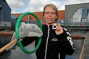 Harbour porpoise Phocoena Phocoena Fjord & Baelt - Meike Linnenschmidt -Auf dem Dritten Bild, tja das bin ich mit einer Demonstration für den Versuchsaufbau meiner Dr.Arbeit. Die Wale werden im Moment dafür trainiert, und solch ein Traing braucht sehr viel Zeit und Geduld, denn ein Trainigsplan besteht aus vielen kleinen Schritten, die man am Ende zusammenfügt wie ein Puzzel, um den Wal zu beten eine Frage zu beantworten. Auf dem Bild wird gezeigt, das ich einen Schweinswal fragen werde in einen Unterwasserring zu schwimmen um sich dort an einem fixen Ort zu positionieren. Von dort aus muss der Wal dann das Wasser vor sich durchorten um das Objekt zu finden (den offenen Zylinder). Der Zylinder wird in verschiedenen Abständen präsentiert. Je weiter weg das Objekt, desto geringer wird das Echo des Obejktes sein, dass zum Wal zurück kommt. Gleichzeitig werden wir mit den EEG-Elektoden die Gehöraktivität überwachen, um zu sehen, ob der Wal weniger Aktivität zeigt im Ghör wenn das Echo schwächer wird, oder ob die Aktivität vielleicht gleich bleibt.