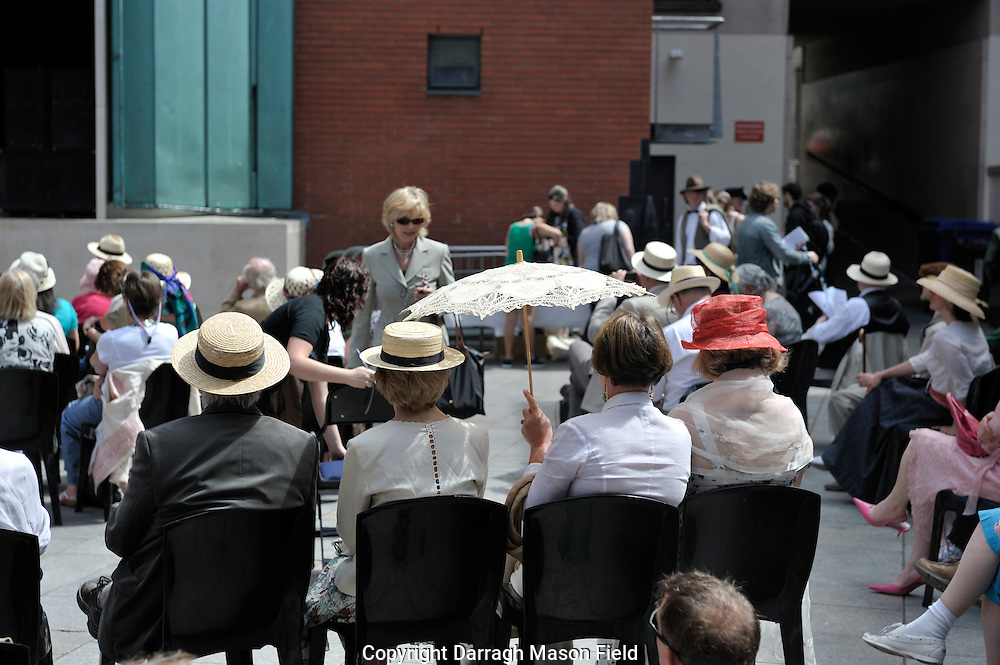 Audience members in costume listening to readings from Ulysses at meeting house square in Dublin on Bloomsday