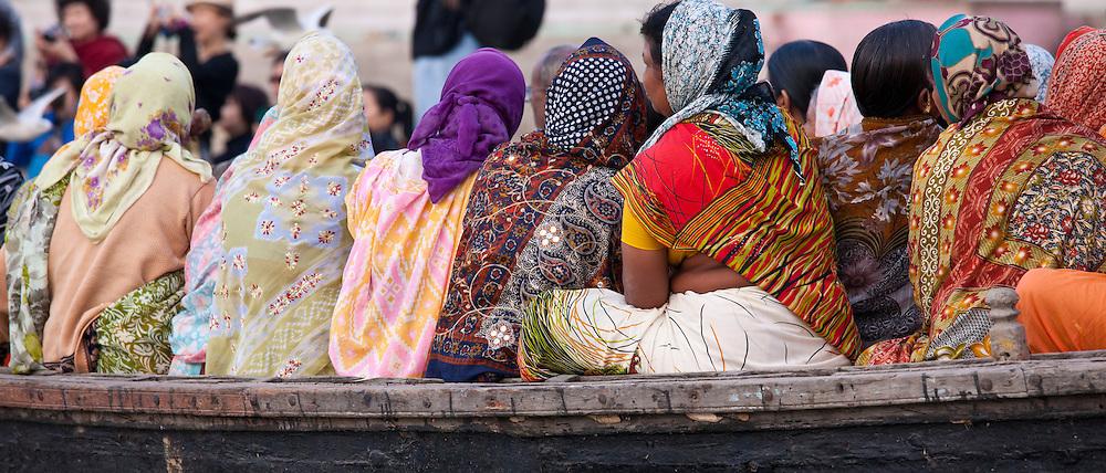 Indian women cruising on the River Ganges and watching ritual bathing by Kshameshwar Ghat in holy city of Varanasi, India