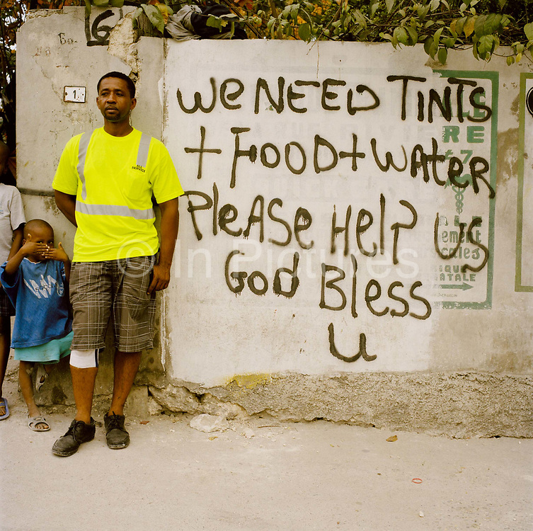 "All around Port Au prince are the hand painted signs and banners shown in the pictures, such was the desperation shortly after the earth quake. Many went without food and water for several days or more. The tragedy is that  it seems many of these requests went largely ignored. Theo Wilder is bemused ""We painted a sign saying we needed food and water in the hope that the aid agencies may be able to help, but no one has helped, not one person."""