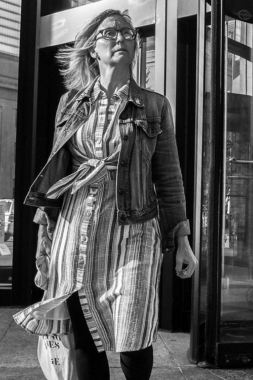 Getting to know a specific part of town is important to making good street images. This photo was the results of knowing that at the end of a working day people emerge from the days work and react favourable to the outside world. I waited in this location many times gathering a few good images, yet this one is special. This woman came through the doors after work and stood and gazed at the outside world. A slight breeze blew and perhaps she enjoyed the fresh air. I love the look of confidence on her face and her hair blowing in the wind. This is a candid portrait that I am sure this person would be happy to have.