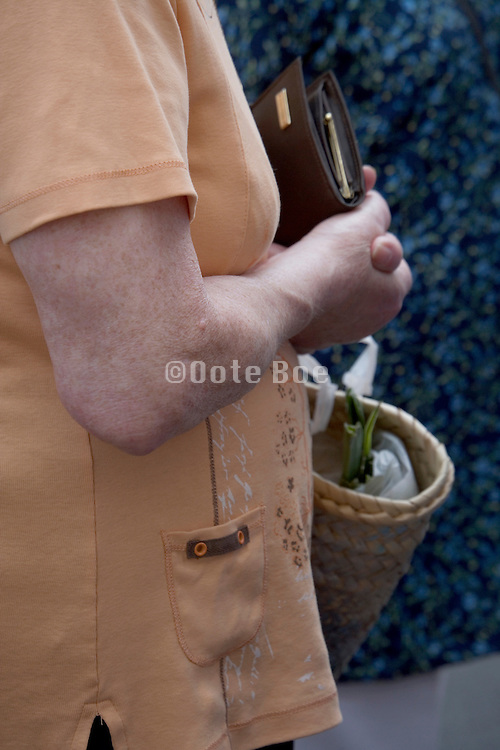 arm of elderly woman holding here wallet and a shopping bag
